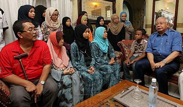 PERDANA Menteri, Datuk Seri Najib Tun Razak bertanya sesuatu kepada Datin Norhaida Abd. Rahim (duduk, empat dari kiri) balu kepada Presiden Kelab Anak Wawasan Pekan (KAWAN), Allahyarham Datuk Rosdi Alizah ketika mengunjungi keluarga tersebut di Taman Jambu Jaya di sini hari ini. Datuk Seri Najib Tun Razak merupakan penaung kelab tersebut.